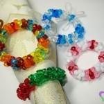 Con perline colorate preparate degli anelli di giusta misura e in questi mettete il tovagliolo.